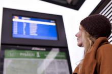Matkustaja katsoo aikataulunäyttöä pysäkillä