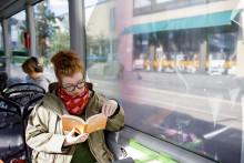 Matkustaja lukee kirjaa Linkki-linja-autossa